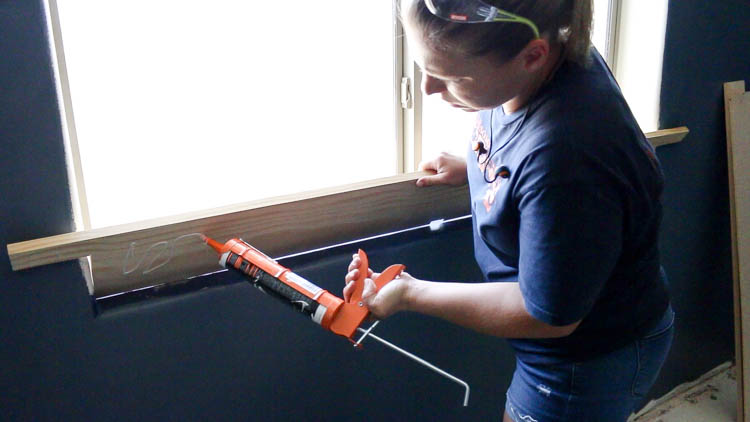 adding adhesive to window sill piece