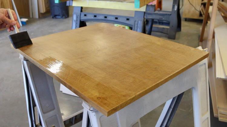 brushing polyurethane on cabinet top-2