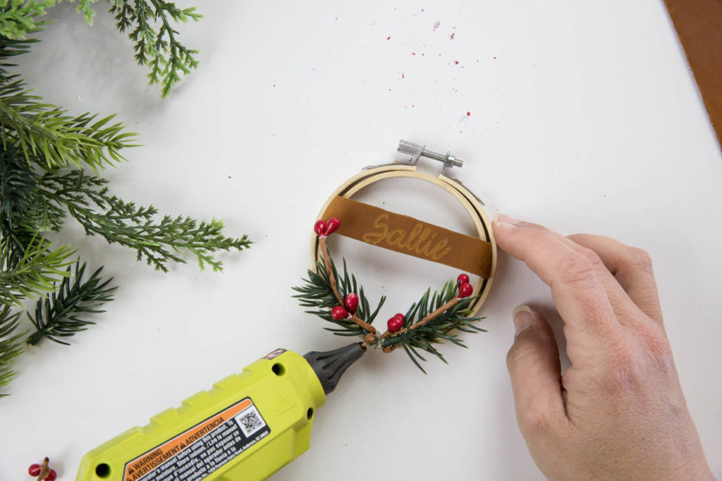 gluing greenery to hoop